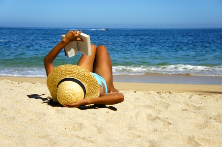 A young woman reading a book on the beach   photo