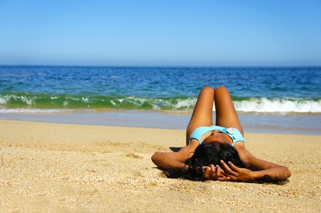 woman laying: Young woman laying on beach sun tanning