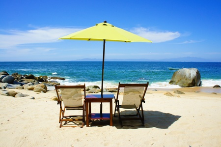Two chairs a table and a yellow umbrella on the beach photo