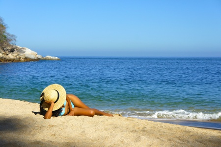 Young woman lying on beach sun tanning. photo