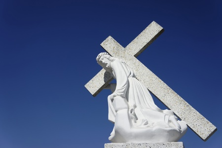 A statue of Jesus carrying the cross on blue sky background. photo
