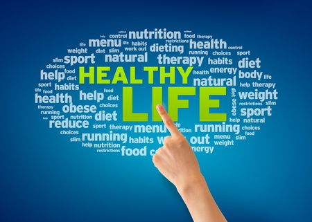 Hand pointing at a Healthy Life word cloud on blue background