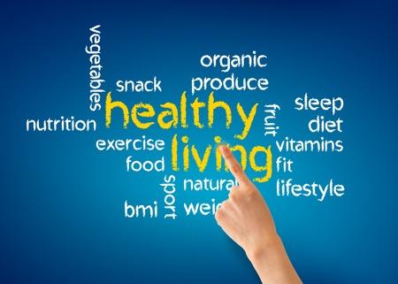 青色の背景に健康的な生活の実例で指している手。 写真素材