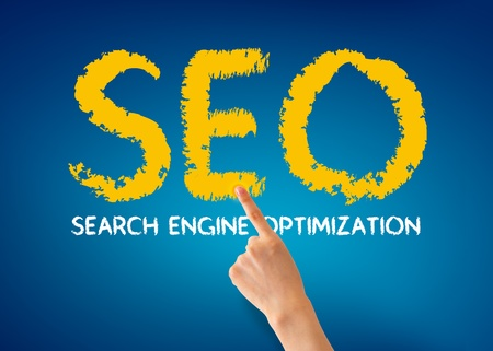 Hand pointing at a Search Engine Optimization word on blue background.  photo