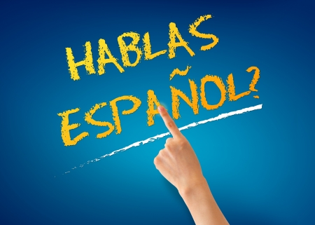 language dictionary: Finger pointing at a Hablas Espanol illustration on blue background.