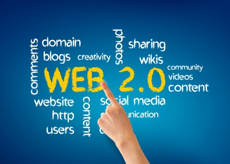 wikis: Hand pointing at a Web 2.0 word illustration on blue background.