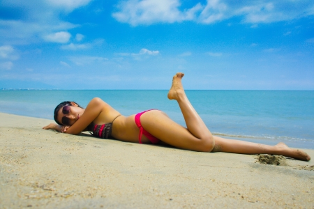 Young woman laying on the beach sun tanning.  photo