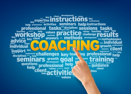 Hand pointing at a Coaching Word Cloud on blue background. Archivio Fotografico