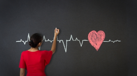 curve line: Woman drawing a Heartbeat Diagram with chalk on a blackboard.