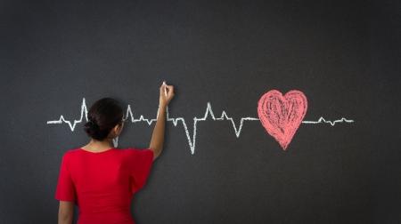 beat women: Woman drawing a Heartbeat Diagram with chalk on a blackboard.