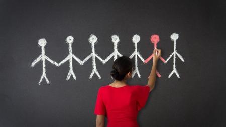 femme dessin: Une femme dessinant une illustration de stickman avec de la craie sur un tableau noir.