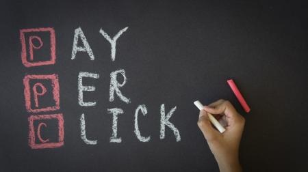 Person writing Pay Per Click with chalk on a Blackboard Foto de archivo