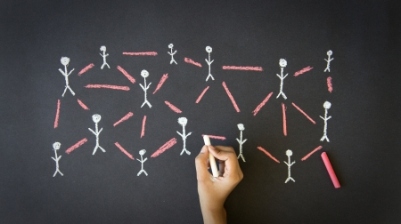 networked: Person drawing a People Network illustration with chalk on a blackboard.  Stock Photo