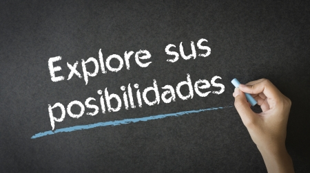 possibilities: A person writing Explore Your Possibilities with chalk on a blackboard
