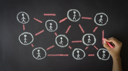 Person drawing a People Network illustration with chalk on a blackboard.  Stock Photo