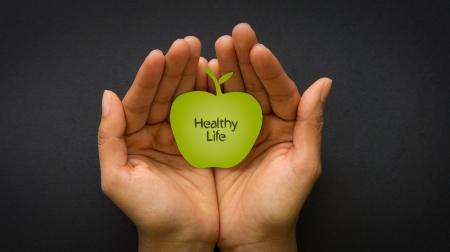 黒の背景に健康的な生活リンゴを持っている手 写真素材