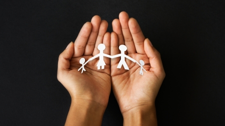 Hands holding a cut out paper family.  Stock Photo