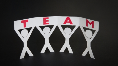 Cut out Paper silhouettes holding a Team sign up in the air. Stock Photo - 18342547