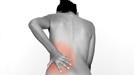 nude woman back: A woman having pain and rubbing her lower back.