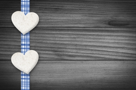 Two hearts and a blue checkered texture stripe laying on wood  photo
