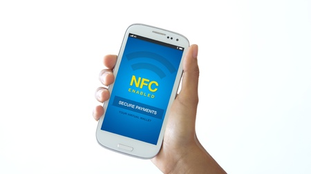 nfc: A person holding a NFC enabled mobile phone