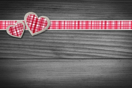 two hearts: Two hearts and a red checkered texture stripe laying on wood