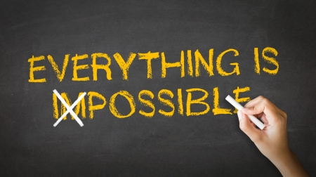 possible: A person drawing and pointing at a Everything is Possible Chalk drawing
