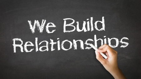 A person drawing and pointing at a We Build Relationships Chalk Illustration