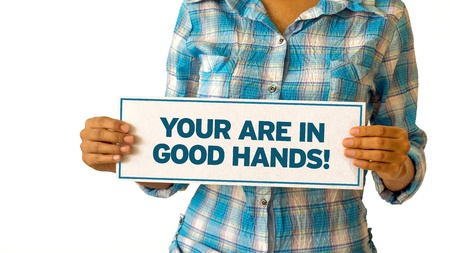 A woman holding a You are in Good hands sign.