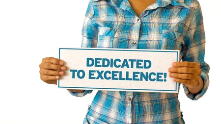 dedicated: A woman holding a Dedicated To Excellence sign.