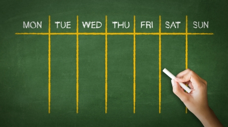 A person drawing and pointing at a Weekly Calendar Chalk Drawing Stock Photo - 21604774