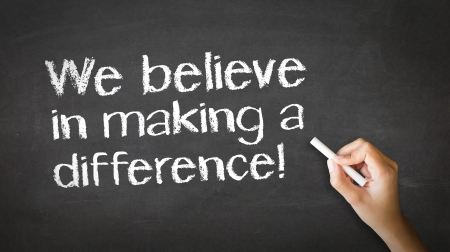 different strategy: A person drawing and pointing at a We believe in making a difference Chalk Illustration Stock Photo