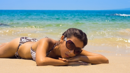 A young woman relaxing on a beach with waves in the background  photo
