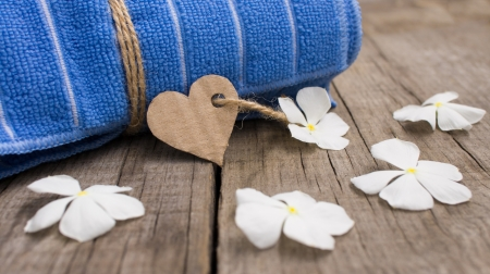 unwind: A towel with a paper sign and flowers on wooden background Stock Photo