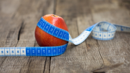 Measuring tape wrapped around a red apple on wooden background. Stock Photo - 21604848