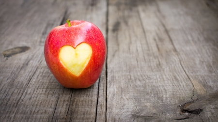 Apple with engraved heart on wood background