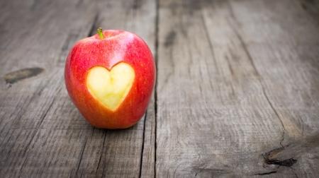 Apple mit gravierten Herzen auf Holz Hintergrund Standard-Bild - 21604862