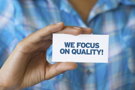 A person holding a white card with the words We focus on quality photo