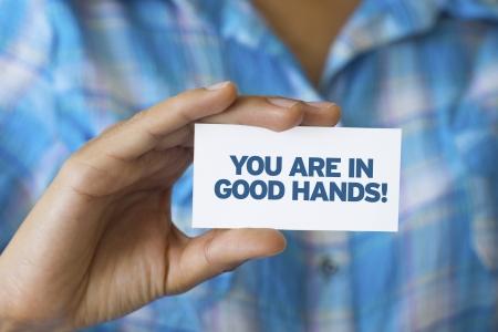 slogan: El titular de una tarjeta blanca con las palabras que estás en buenas manos Foto de archivo