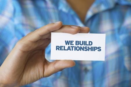 Een persoon die een witte kaart met de woorden Wij bouwen relaties