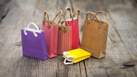 Kleurrijke miniatuur papieren boodschappentassen op hout achtergrond.