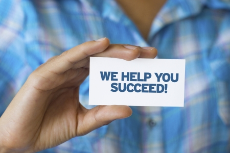 A person holding a white card with the words We help you Succeed Stock Photo - 21604916