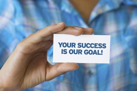 A person holding a white card with the words Your success is our goal Stock Photo - 21604917