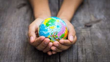 A person holding a globe on wooden background. Standard-Bild