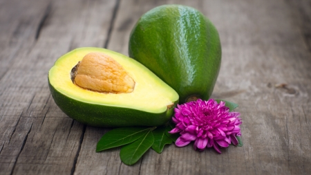 Avacado fruit with green leaves and flower on wood background