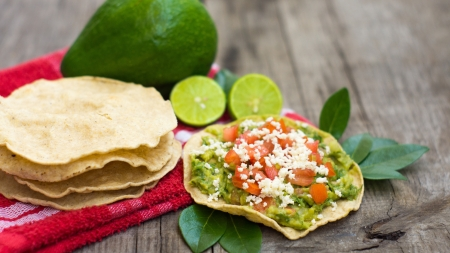 Mexican Tostadas with avocado and lemon on wooden background. Standard-Bild