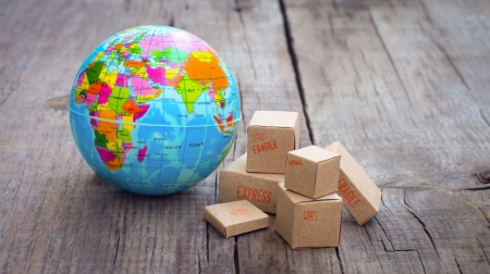 international shipping: Miniature globe and boxes on wooden background