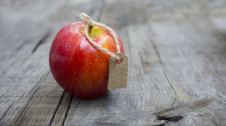 achievment: A Red Apple with a Price Label on wood background Stock Photo