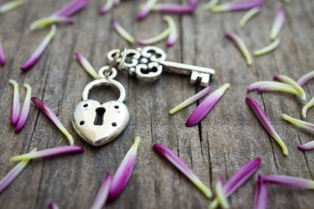 lock and key: Key with heart shaped lock charm on wooden background.
