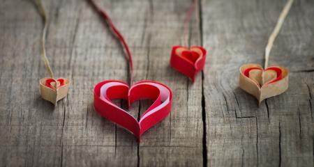 verlobt: Vier Büttenpapier Herzen auf hölzernen Hintergrund.